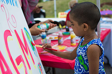 Child painting at Pride Event